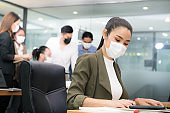 Portrait of Asian woman office worker wearing face mask working in the new normal office and doing social distancing during coronavirus COVID-19 pandemic