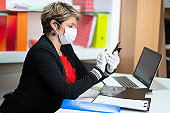 Woman in the office texting on smart phone with protective face mask on
