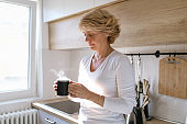Woman enjoying steaming cup of tea in her kitchen