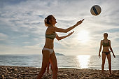 Young woman serving in beach volleyball match at dusk
