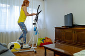 Woman with remote exercising on elliptical trainer at home