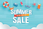 Summer sale with decoration origami hanging on blue wooden background. Paper art and craft style.