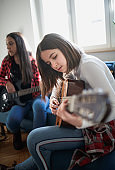 Teenager girl holding acoustic guitar determined to learn chords