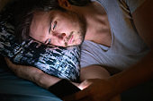 Young man in bed at night unable to sleep using his mobile