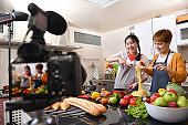 Mother and daughter blogger vlogger and online influencer recording video content on healthy food
