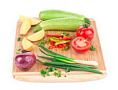 Still life with various ripe vegetables on cutting board.