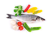 Still life with fresh seabass and vegetables.