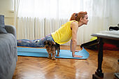 Woman practicing plank position in the living room while dog is playing around