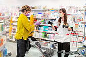 Female customer holding disinfectant on safe distance from clerk