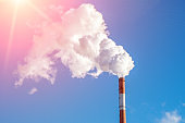 industrial smoke from a chimney in the blue sky. space for text, copy space
