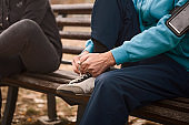 Senior couple tying sport shoe shoelace in the park getting ready for sport