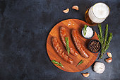 Raw meat beef sausages for grill and spicy, herbs rosemary, pepper, salt on table