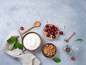 natural healthy superfood fermented yogurt with granola, chia seeds and  cherry  on light  table