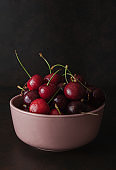 Cherry on bowl on stone table.