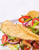 two Mexican tacos with chicken, onions, chili peppers,  corn and beans on a serving plate on white background