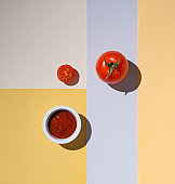 fresh sweet juicy tomato and ketchup on multicolored backgrounds with hard shadow.