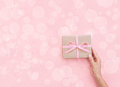 Female hands holding present box or gift box package in craft paper
