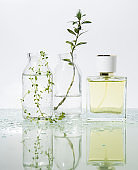 manufacturer of perfume. Several glass vessels with perfumed water and flowers on a mirrored table