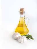 Rosemary twig and garlic, olive oil on bottle isolated on white background.