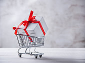 holiday white box with red ribbon in shopping cart on gray background