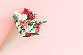 Roses bouquet in cone on pink background, flat lay, top view.