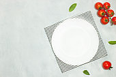 White empty plate and napkin on grey stone table top view