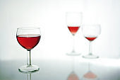 Drinking glass with red wine in the foreground, two more blurred further back, light gray blue background with copy space, selected focus