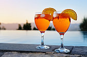 two glasses with Spritz Veneziano, an Italian cocktail drink from aperol, prosecco and soda on a wall at the water against a clear sunset sky, copy space