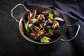 Blue mussels ready to eat, cooked in a metal pot with onions, white wine and parsley garnish, dark background with copy space, selected focus