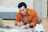 Contented man working with documents at home and smiling