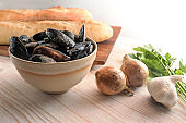 Fresh raw mussels and ingredients like onion, garlic, parsley and baguette bread for a Mediterranean appetizer dish on a bright wooden table, copy space