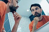 Thoughtful man in front of the mirror at home