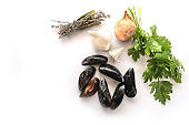 Ingredients for a Mediterranean meal with fresh blue mussels, onion, garlic, parsley and dried herb bouquet, white background with copy space, high angle view from above