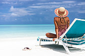 Rear view of a woman relaxing on a deck chair at the beach.