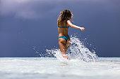 Back view of carefree woman splashing water while running through sea.