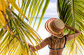 Back view of a woman with sun hat among palm leaves on the beach.