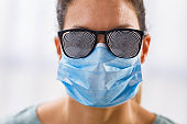 Fearful woman with protective face mask unable to see the reality.