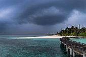Beach of Velassaru, Maldives under moody sky.