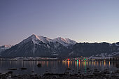 Lake Thun and the mountain Niesen during twilight with reflection of little village lights in the lake.