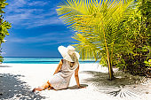 Back view of a woman with sun hat relaxing on the beach.