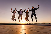 Playful business colleagues jumping on a rooftop at sunset.