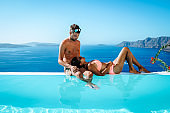 couple on a luxury vacation in Greece, Oia Santorini men and woman at caldera infinity pool looking out over the ocean of Santorini Island