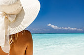 Rear view of a woman with sun hat looking at sea view.