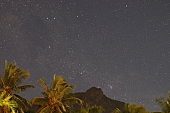Tropical landscape with mountains and starscape.