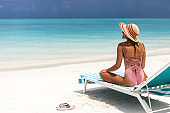 Happy woman with sun hat relaxing on a deck chair at the beach.