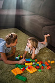 Happy single mother and son playing with toy blocks on carpet at home.