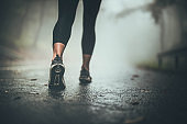 Close up of unrecognizable athlete walking during foggy day.