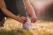 Close up of sports woman tying shoelaces in nature.