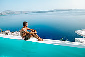 Santorini greece, young men on a luxury vacation at the Greek Island of Santorini