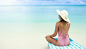 Rear view of a woman with sun hat sitting on a deck chair in shallow water.